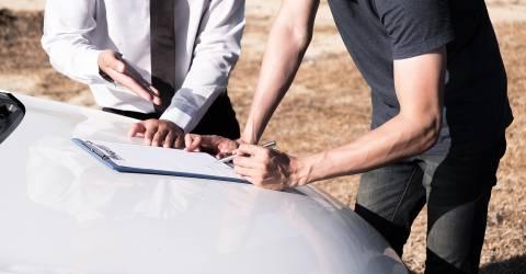 Verzekeringsagent en de eigenaar van de auto tekenen de overeenkomst voor een schadeclaim